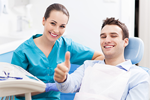 Man with straight teeth in dental chair giving thumbs up